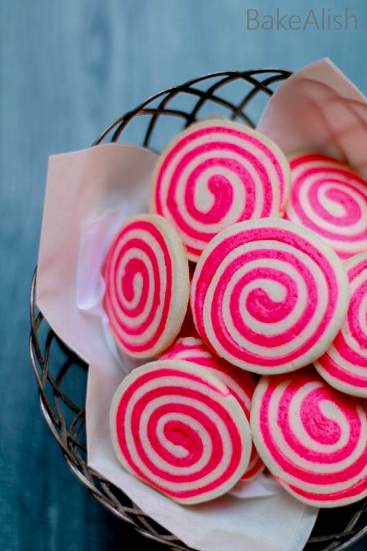 These Pinwheel cookies are perfect for Valentine's day and Christmas as well. Learn how to make pinwheel cookies with red and white cookie dough in a step by step method on how to roll pinwheel cookies