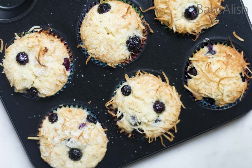 Blueberry muffins with coconut flakes on it that are moist and easy to make