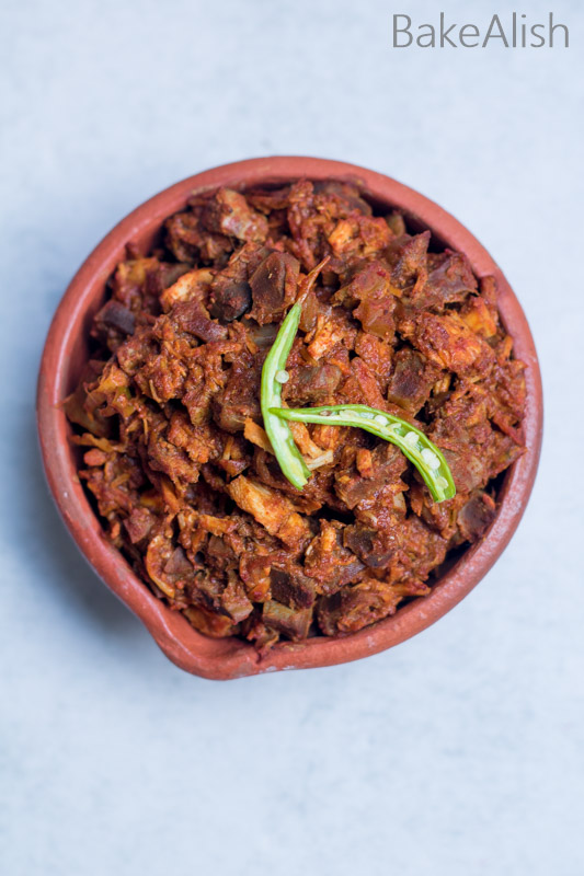 East indian meat with green chili's on it made with bottle masala in an earthen pot
