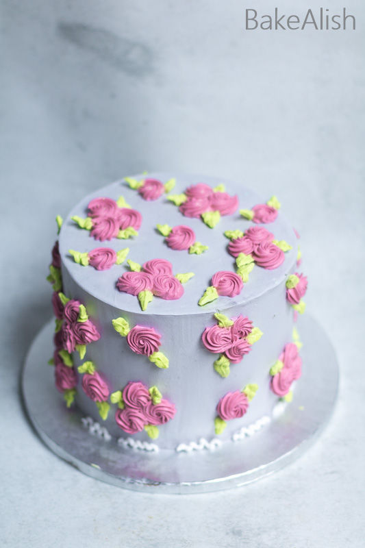 tall grey pink whipped cream cake with flowers and leaves