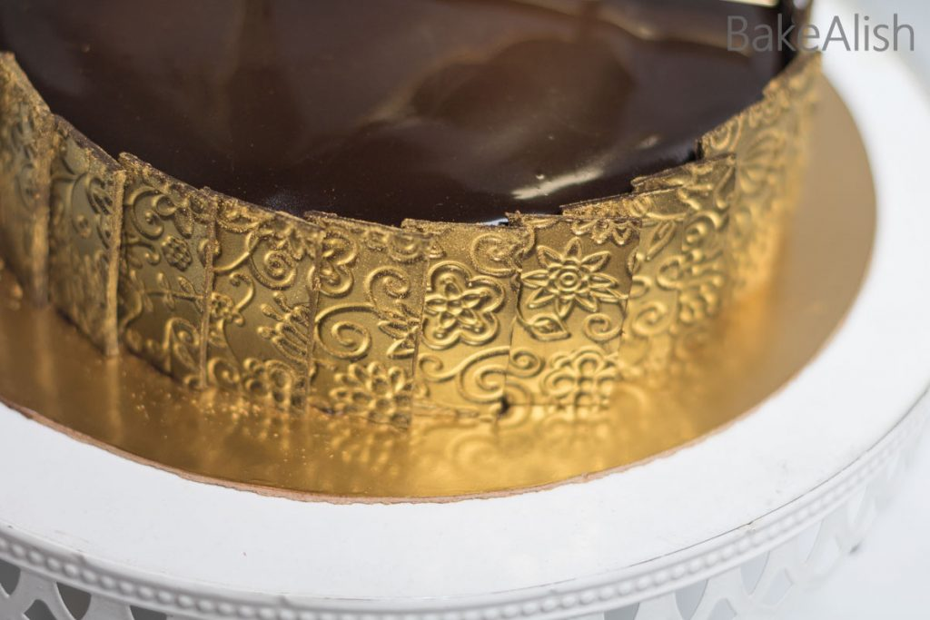chocolate gold lace with chocolate mirror glaze cake on a golden color board