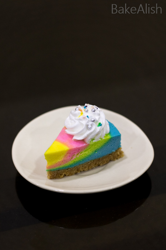 rainbow cheesecake on a white plate