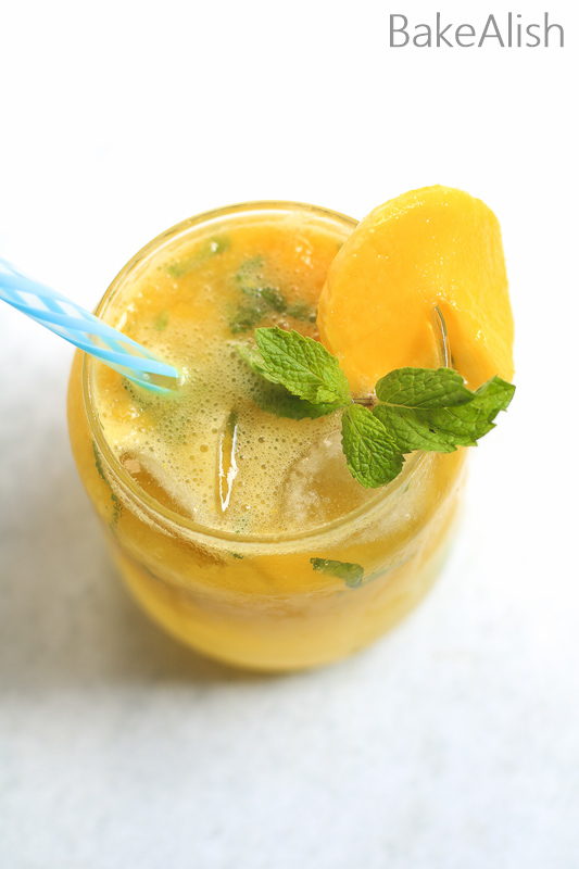 orange color mocktail in a glass with mint and mangoes