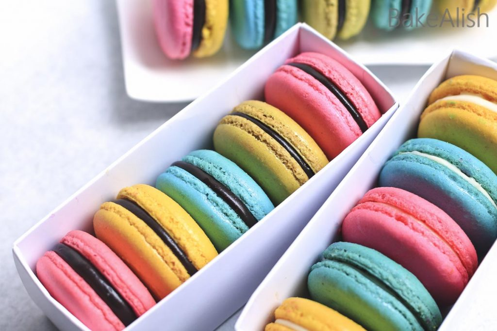 white color macaron boxes with pink yellow blue green macarons